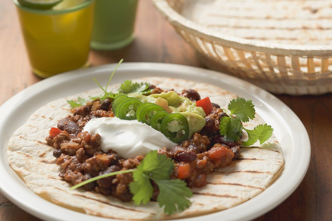 Mince and bean filling with sour cream on tortilla