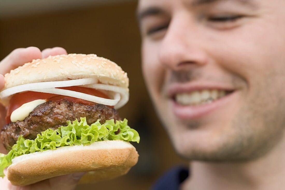 Man holding large hamburger