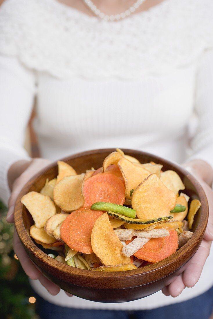Woman holding wooden bowl of vegetable crisps