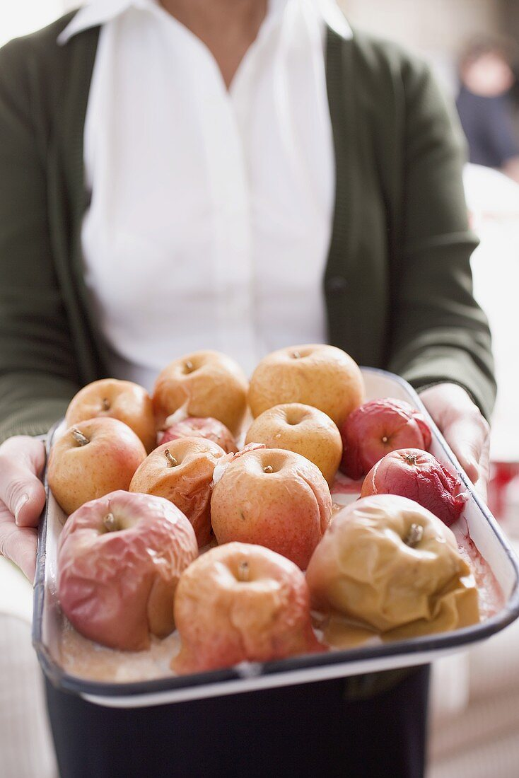 Woman holding baked apples on baking tray