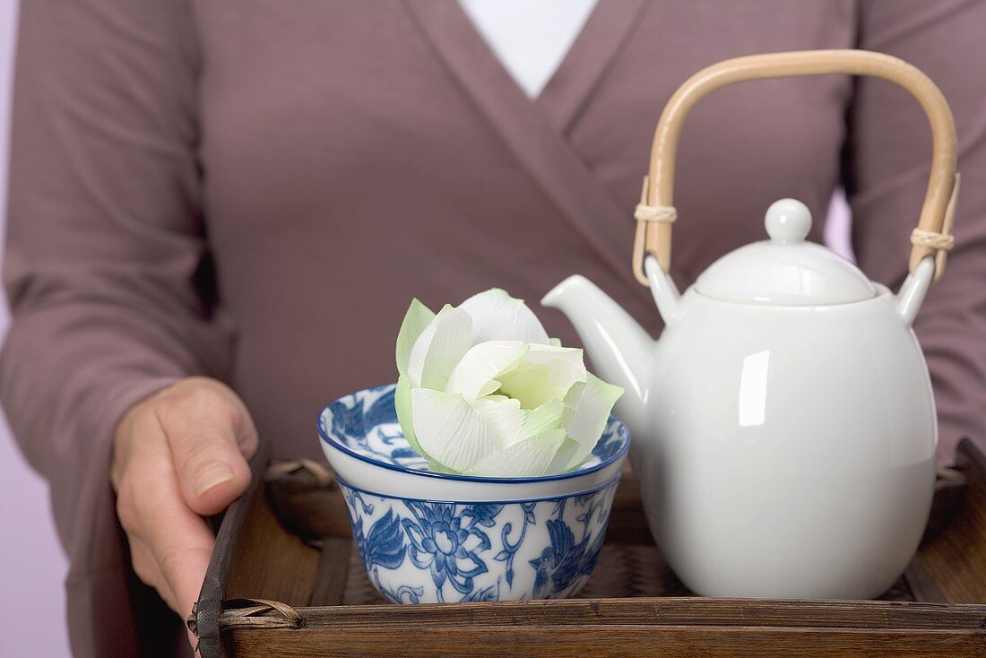 Woman holding tray of tea things (teapot, tea bowl, flower)