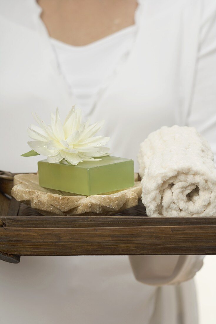 Woman holding soap, water lily and towel on tray