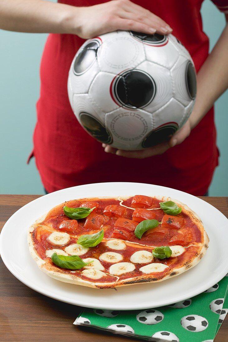 Tomato & mozzarella pizza, female footballer in background