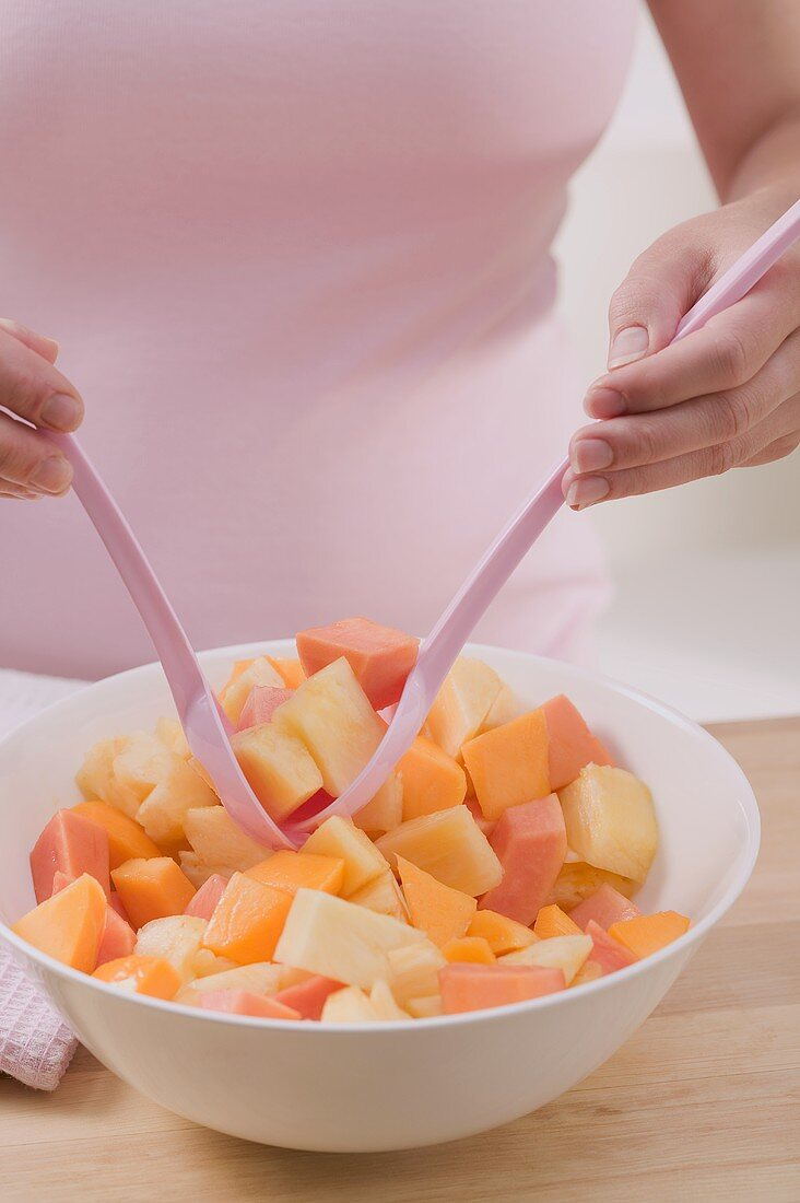 Woman taking fruit salad out of bowl with salad servers