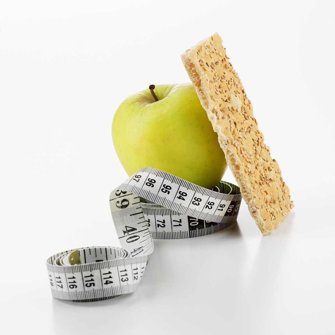 Green apple and crispbread with tape measure