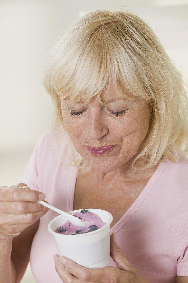 Woman eating blueberry yoghurt