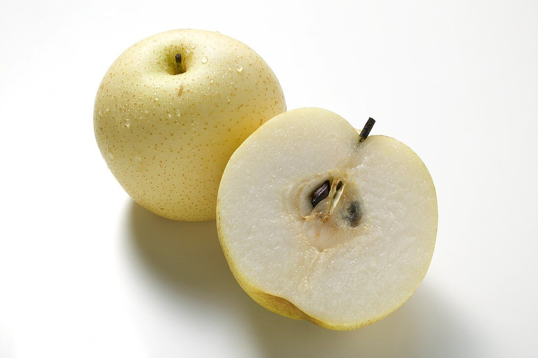 Whole Nashi pear and half a Nashi pear (overhead view)