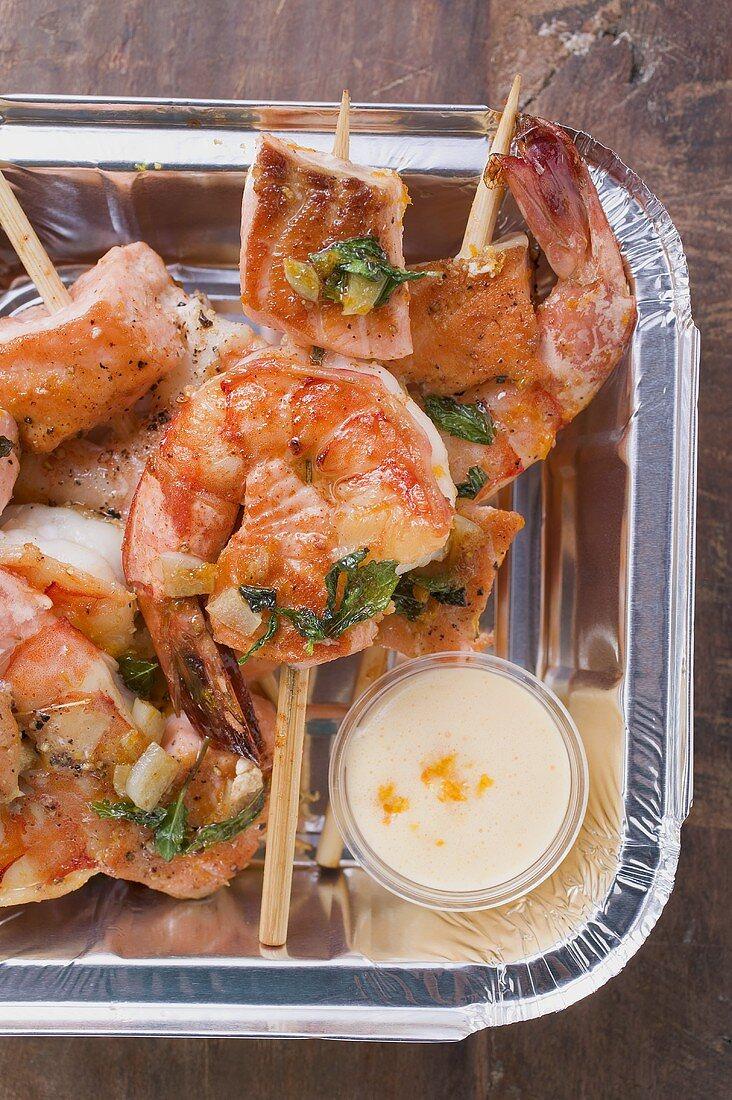 Salmon & prawn skewers with mint & sauce in aluminium dish