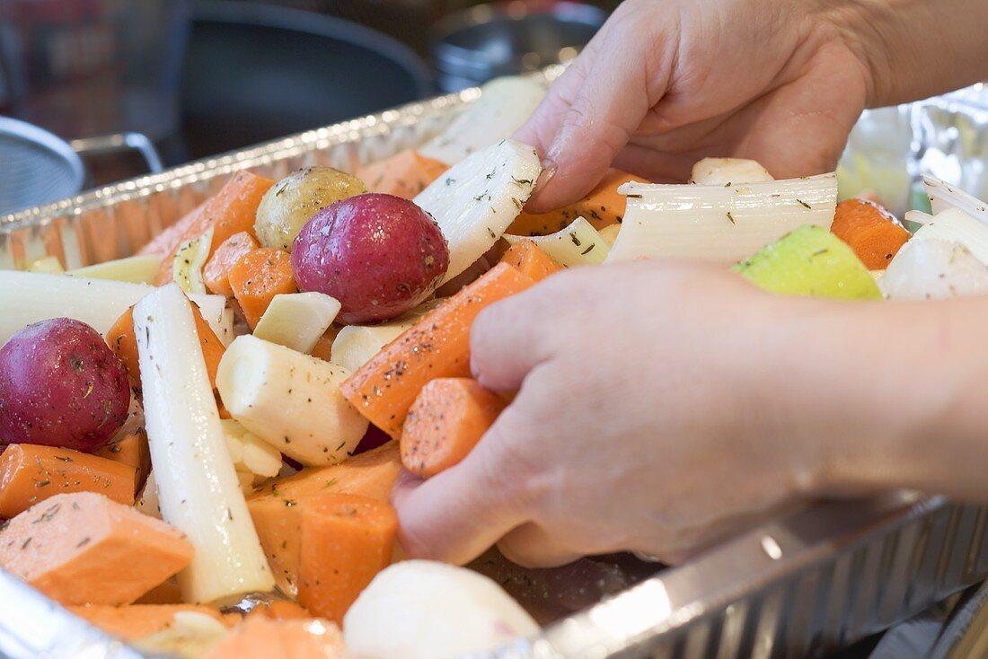 Hands arranging root vegetables in aluminium dish