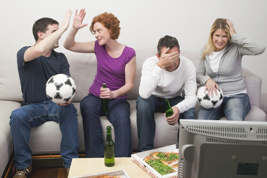 Friends in front of TV with footballs, beer and pizza