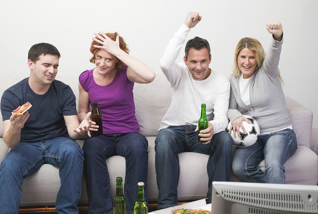 Friends in front of TV with pizza, beer and football