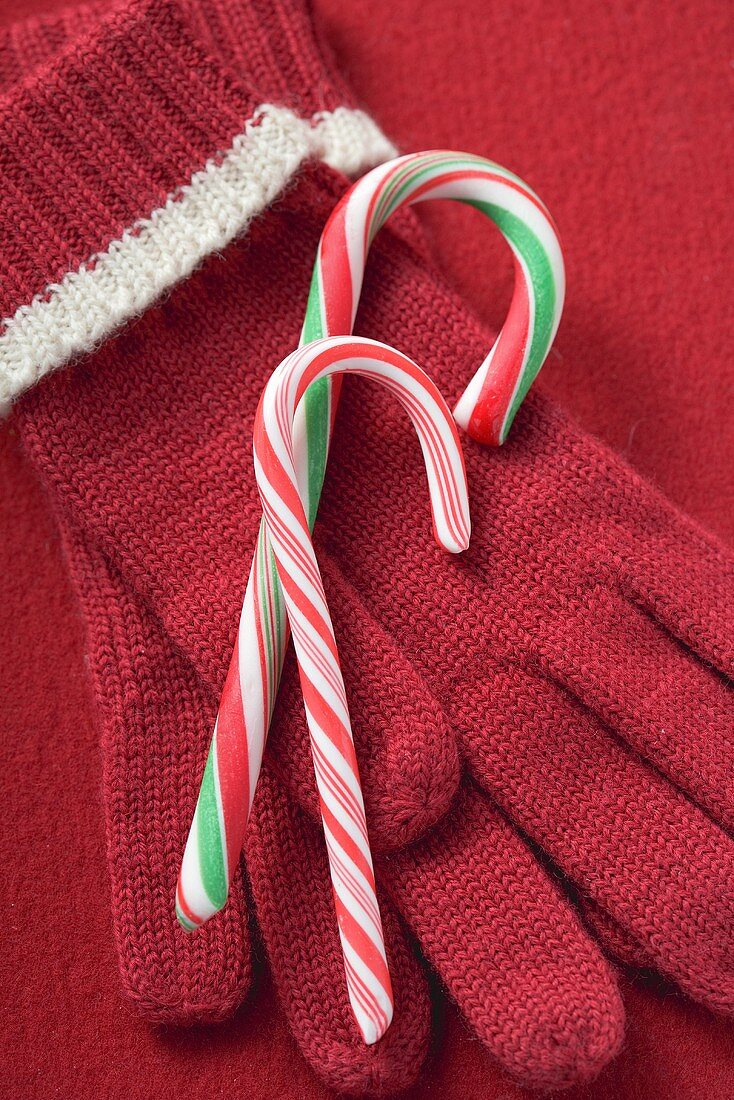 Two candy canes on red gloves