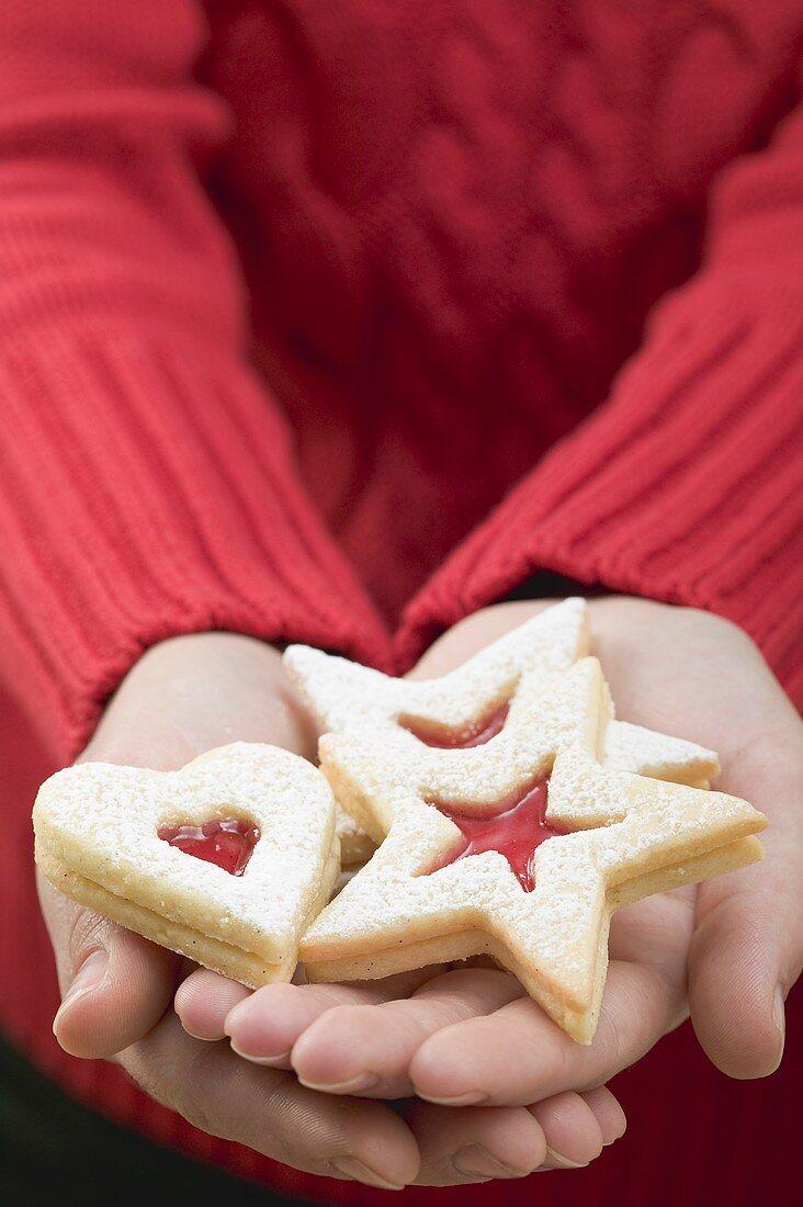 Hands holding jam biscuits