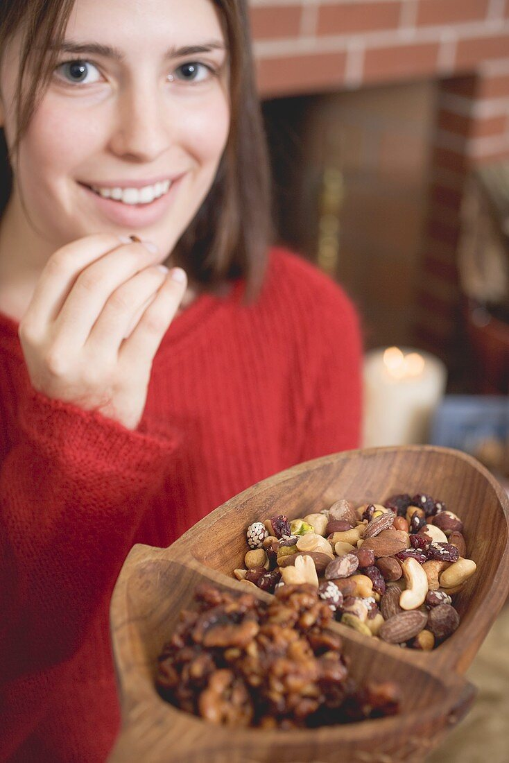 Young woman eating nuts in front of fireplace (Christmas)
