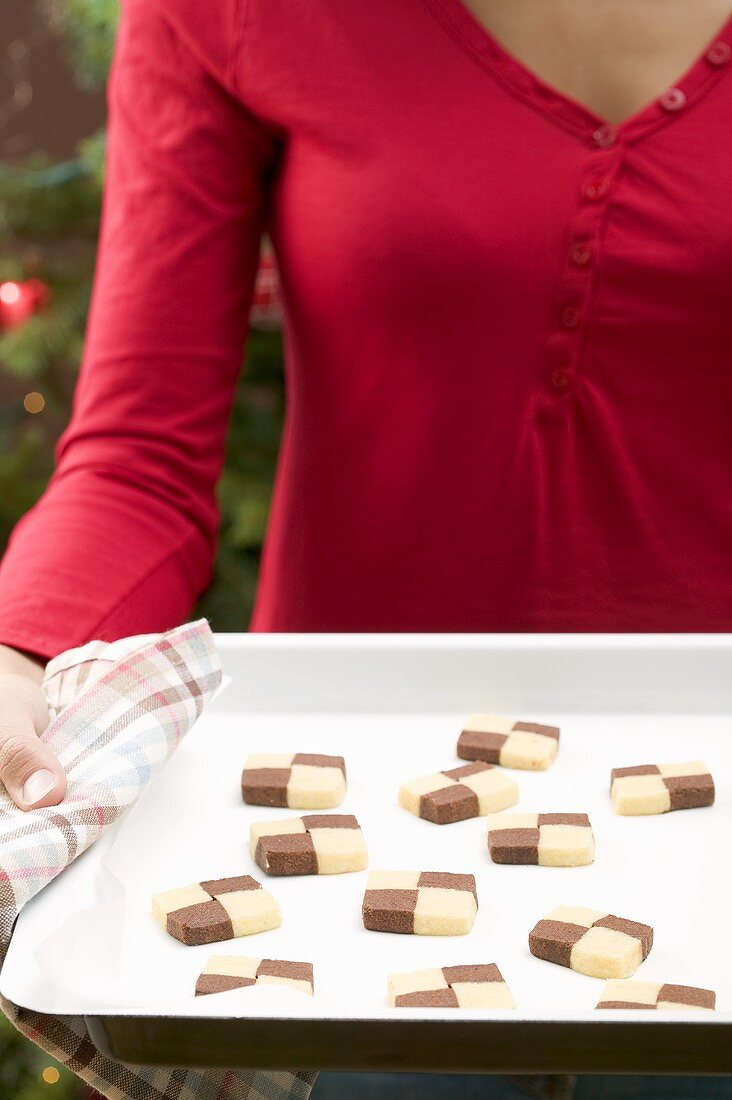 Woman holding baking tray of checkerboard cookies
