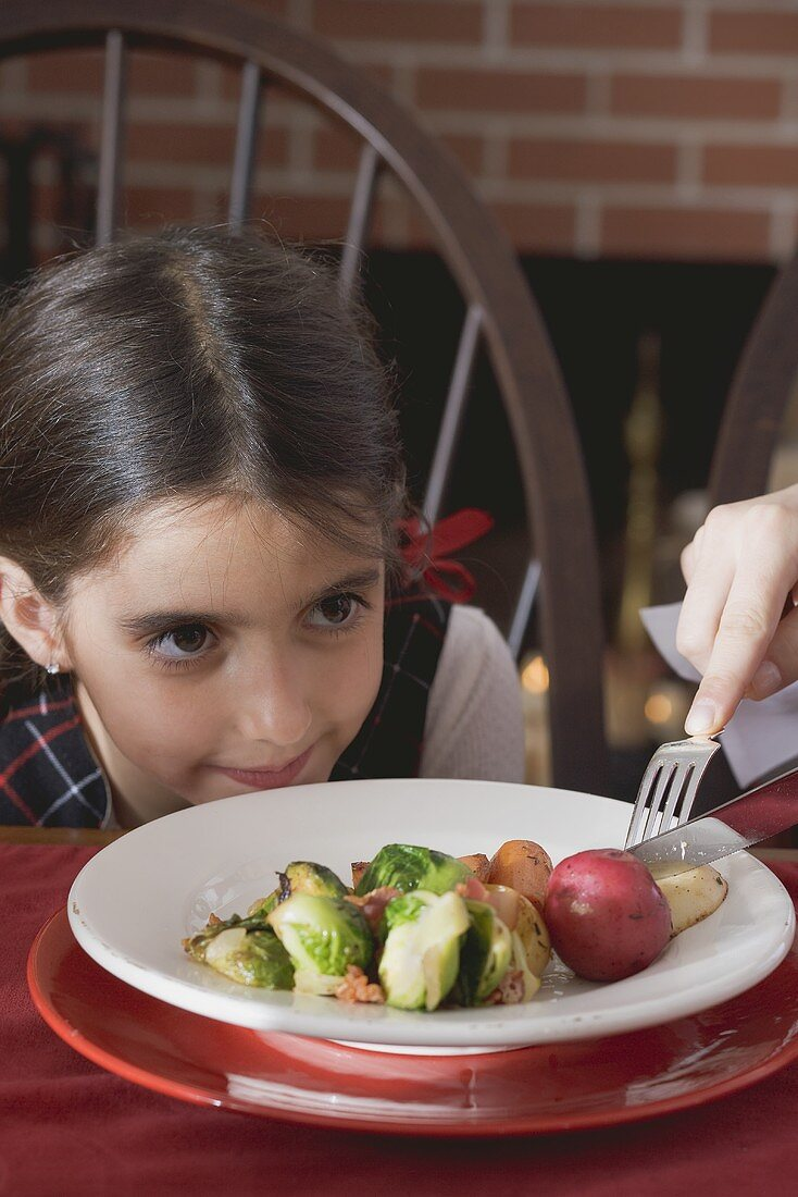 Hand cutting up vegetables on small girl's plate