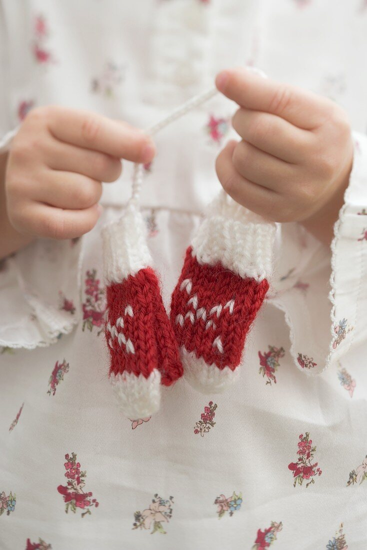 Small girl holding knitted mittens