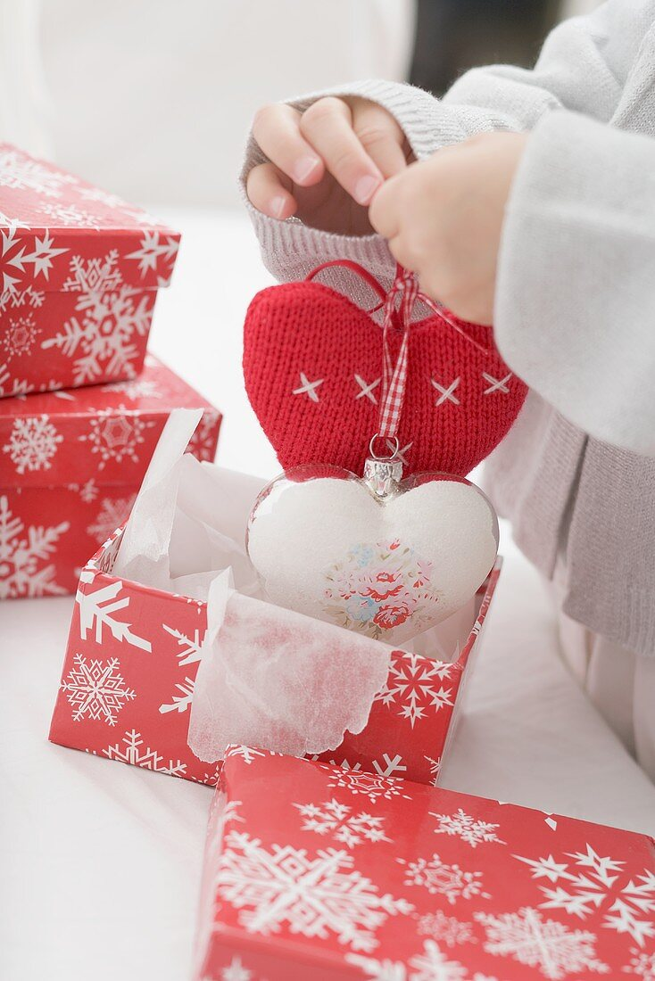 Child taking Christmas tree ornaments out of box