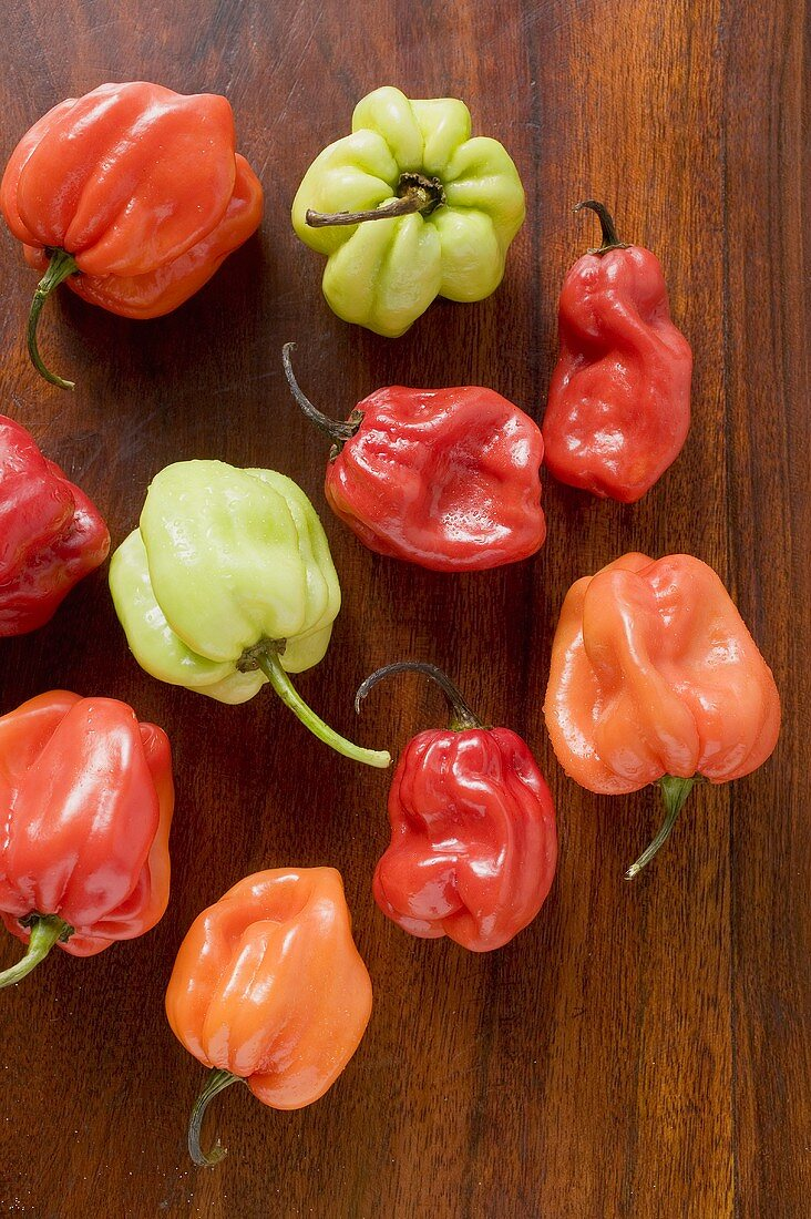 Different coloured Habanero chillies on wooden background