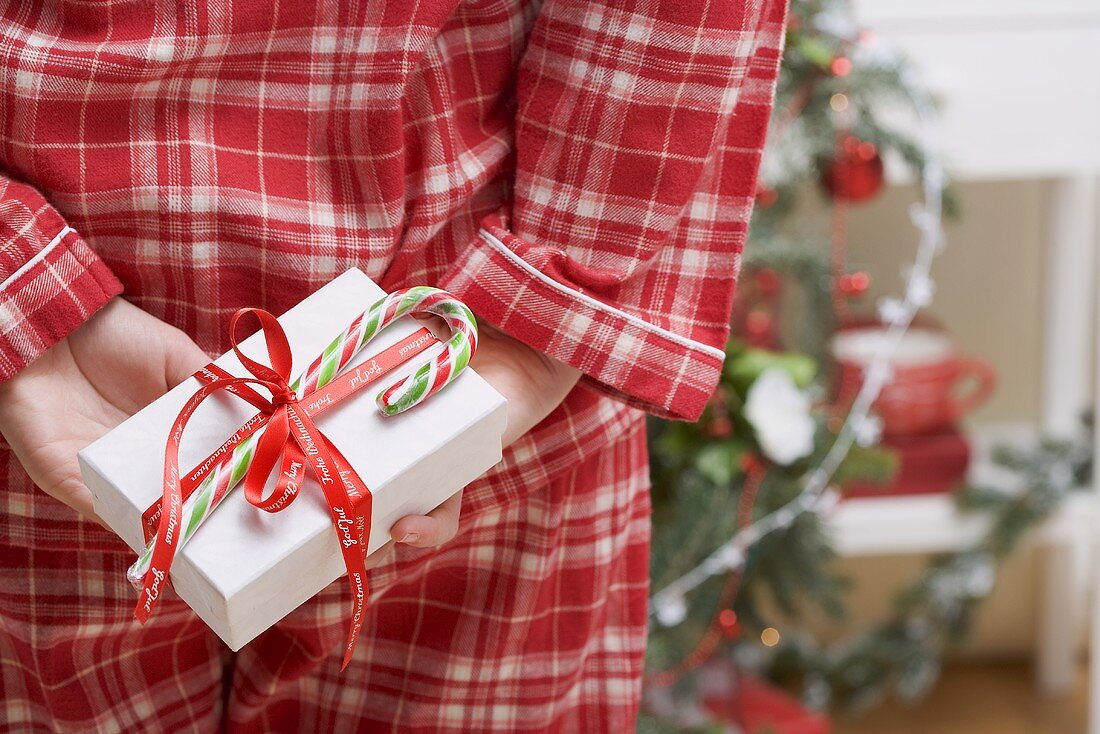 Woman hiding Christmas gift behind her back