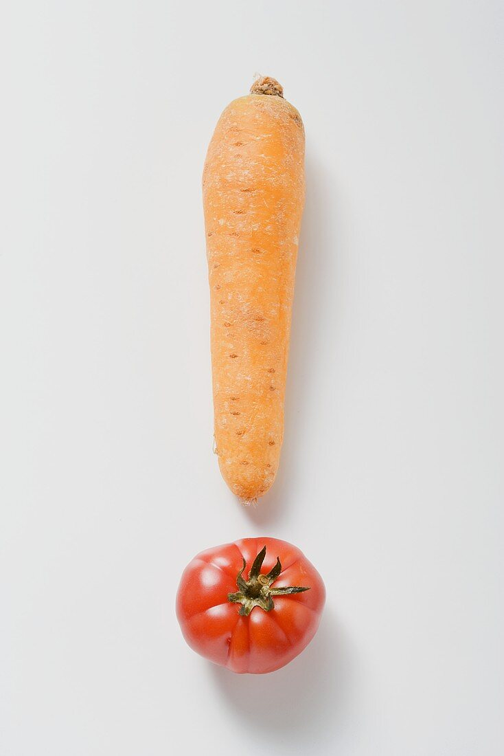 One carrot and one tomato forming an exclamation mark