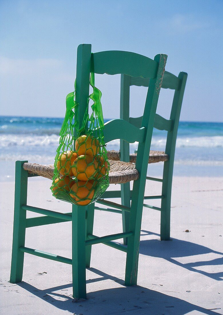 Two chairs, one with oranges, on the beach