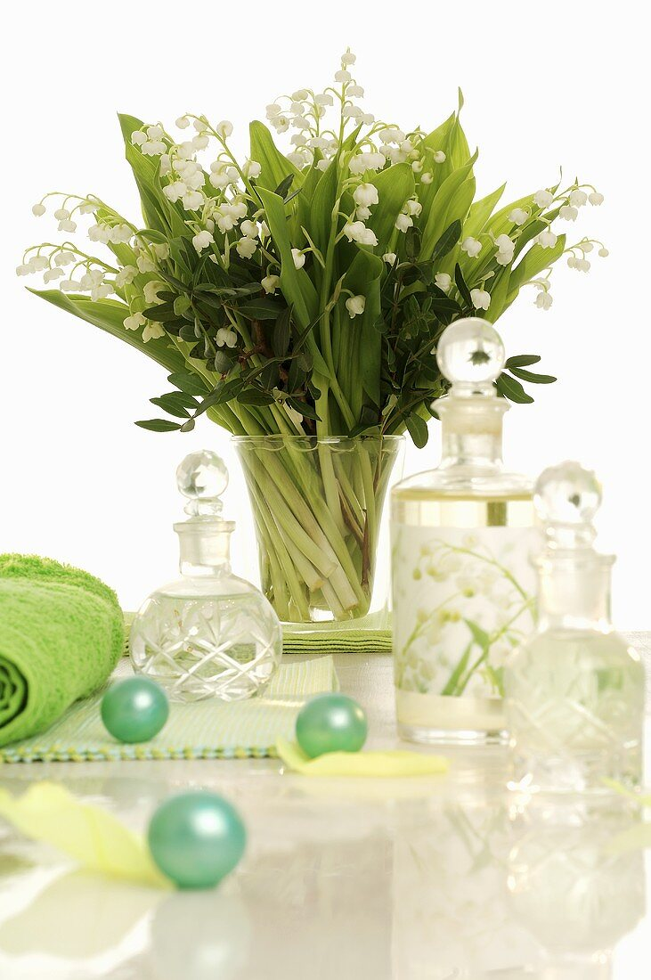 Posy of lilies of the valley & small bottles in bathroom