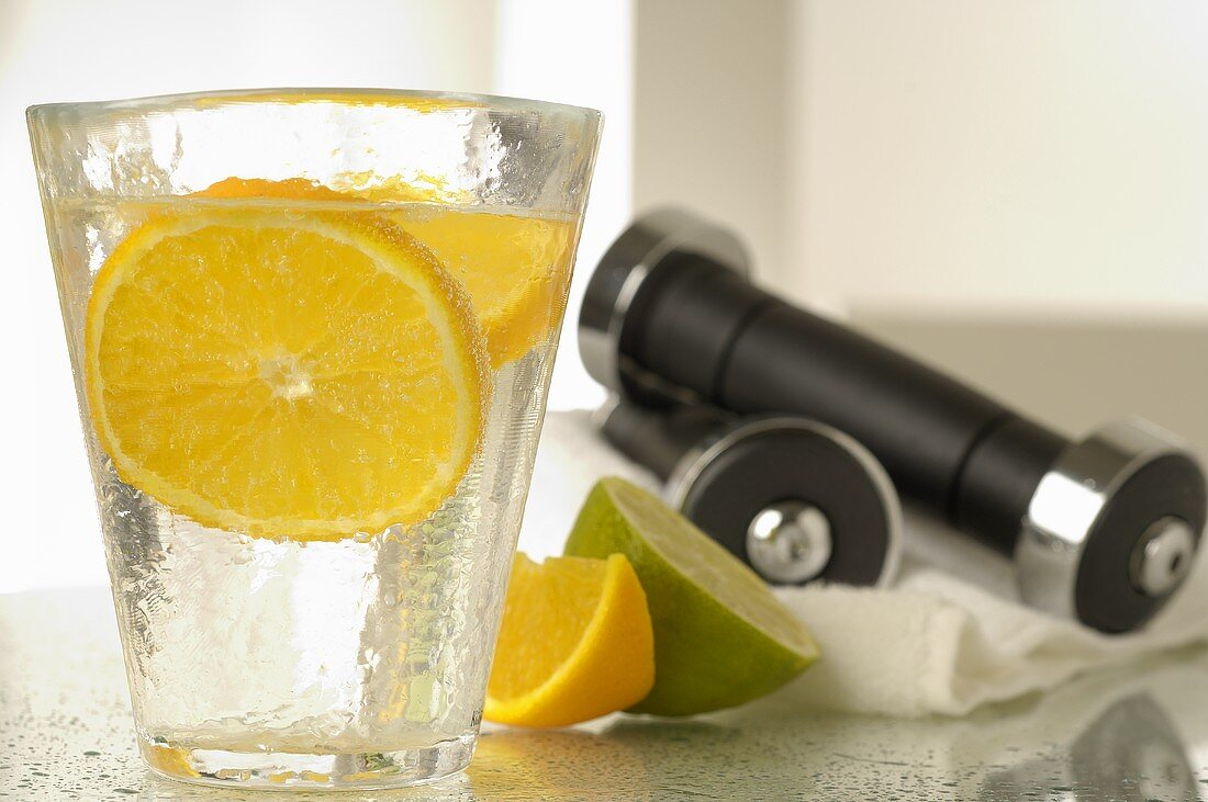 Mineral water with slice of lemon and hand weights