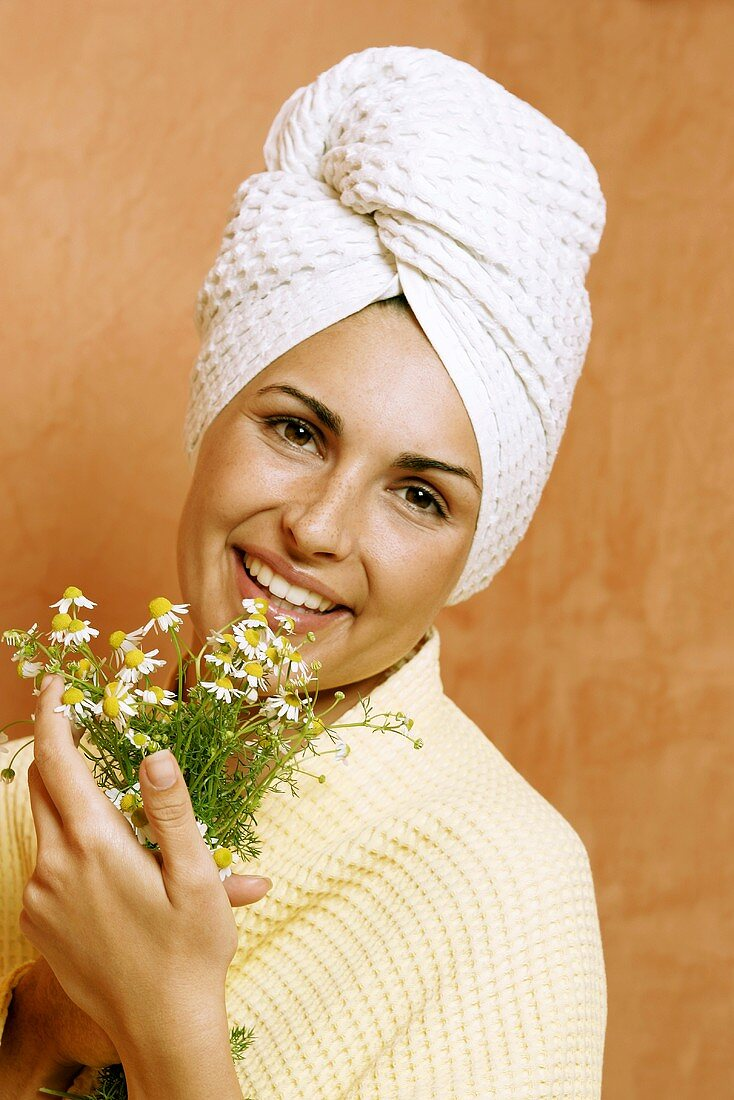 Woman in bathroom with bunch of chamomile