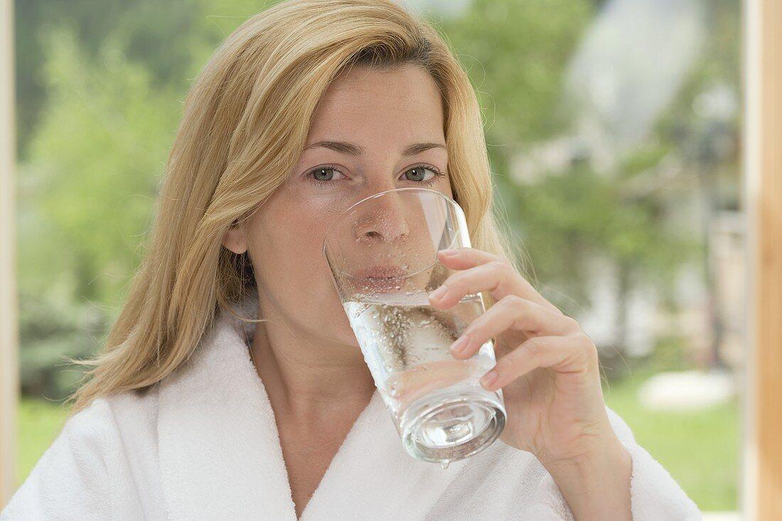 Woman in white bathrobe drinking glass of water in garden