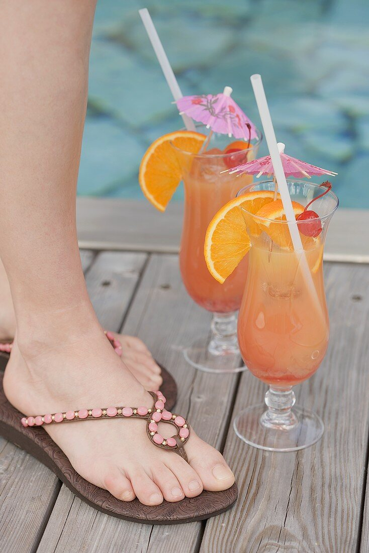 Two cocktails (Planter's Punch) by pool