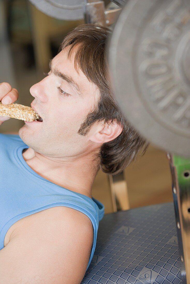 Man eating muesli bar on weight bench
