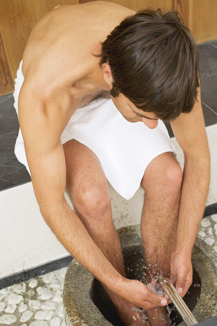 Young man bathing his feet