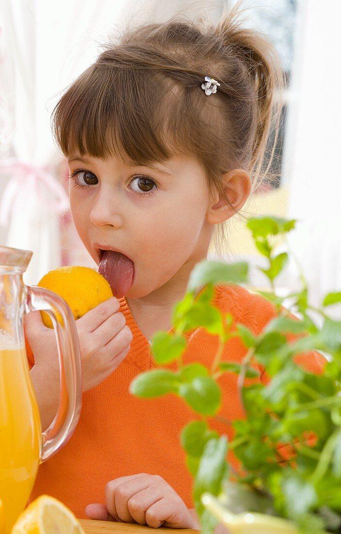 Girl licking a lemon beside jug of lemonade