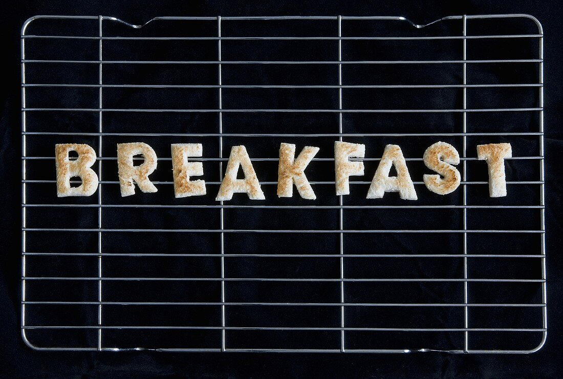Toast letters spelling the word BREAKFAST on a rack