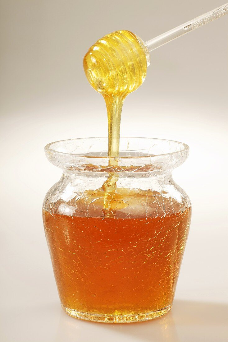 Honey drizzling off an acrylic spoon into a jar