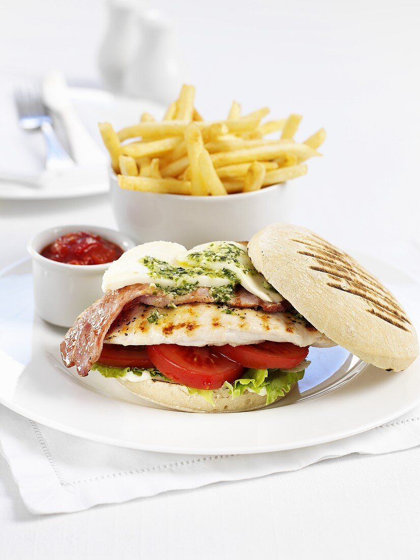 Chicken burger with bacon, mozzarella and pesto and a side of chips
