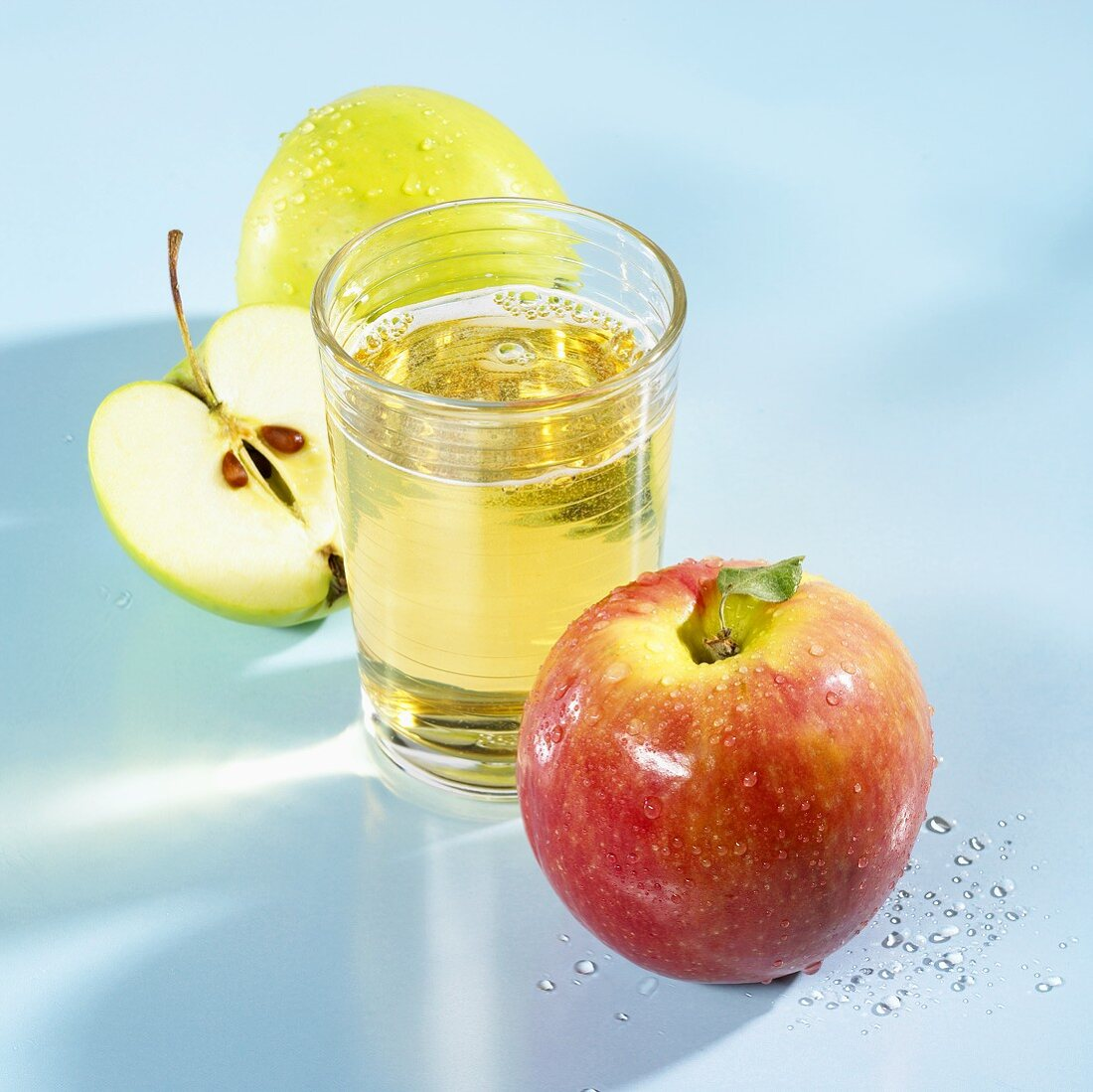 A glass of apple schorle with apples beside it
