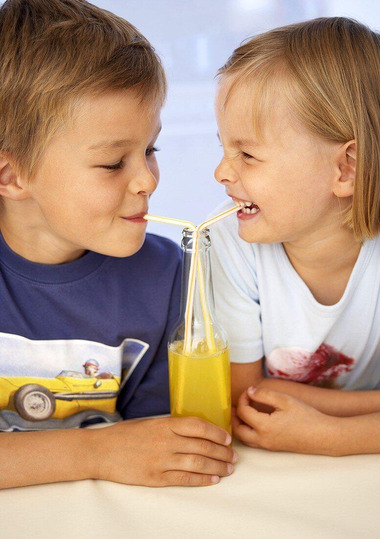 Children drinking orangeade through straws