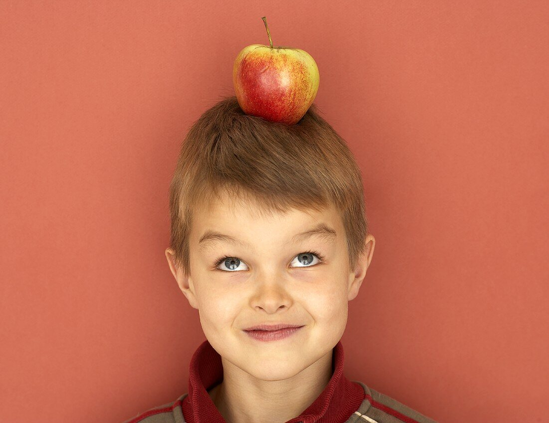 Small boy with apple on his head