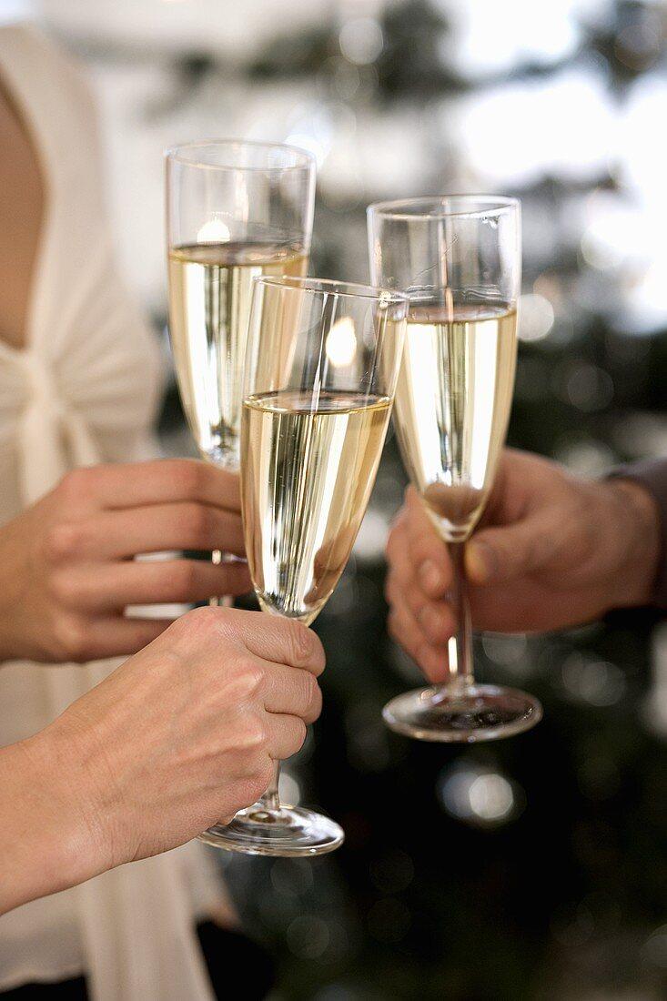 Clinking three champagne glasses