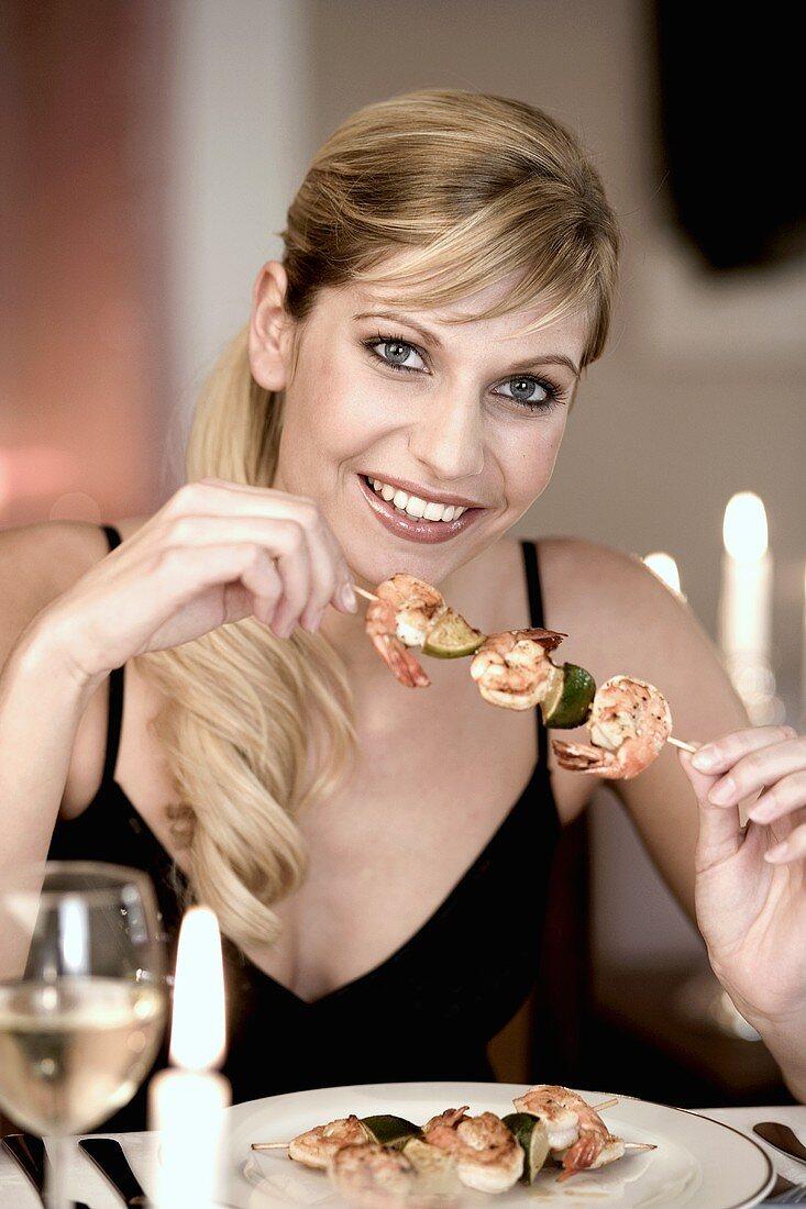Young woman eating a shrimp kebab