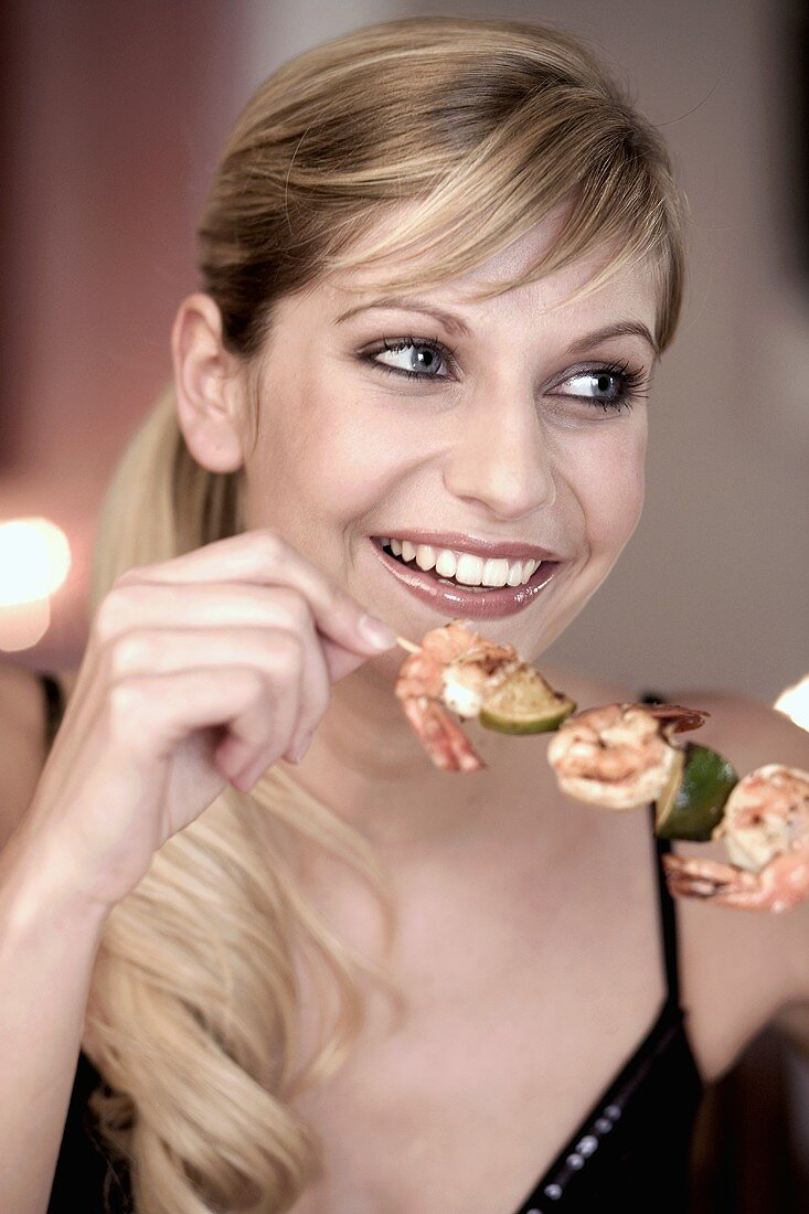 Young woman eating a shrimp kebab