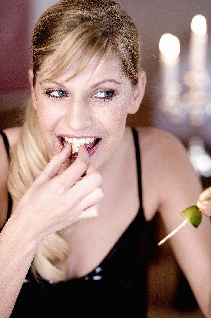 Young woman biting into shrimps on skewer