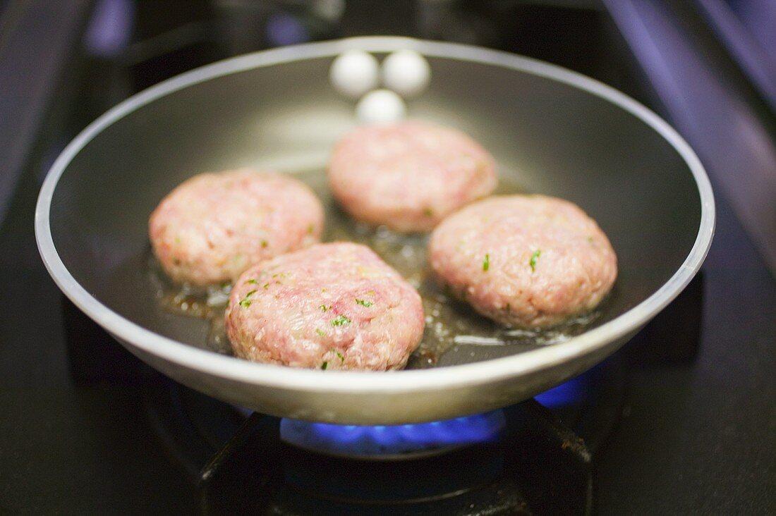 Frying burgers in a frying pan