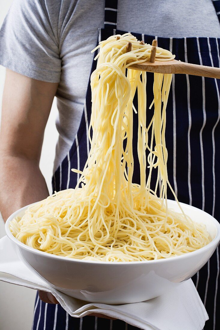Cooked spaghetti in a dish and on spaghetti server