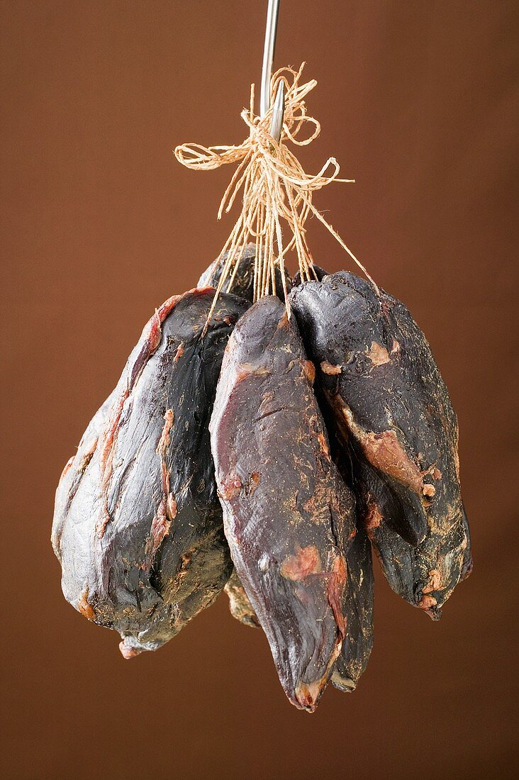 Smoked venison ham on a hook