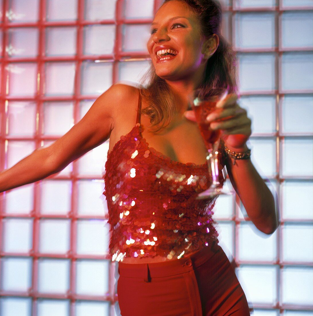 Woman dancing with cocktail in her hand