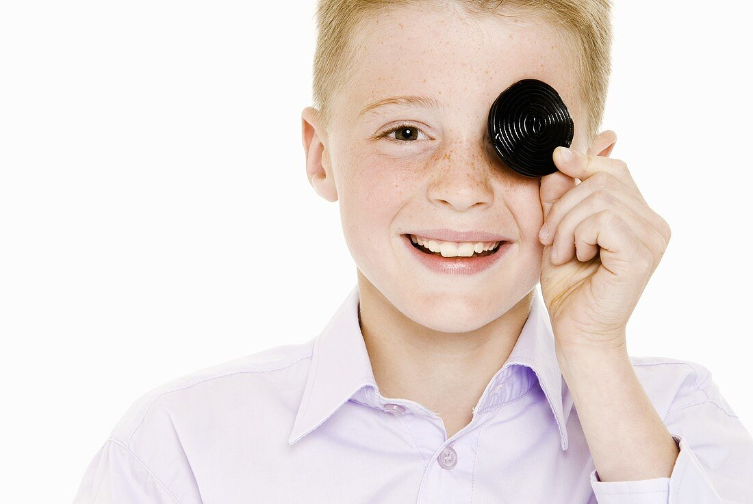 Boy covering one eye with a liquorice wheel