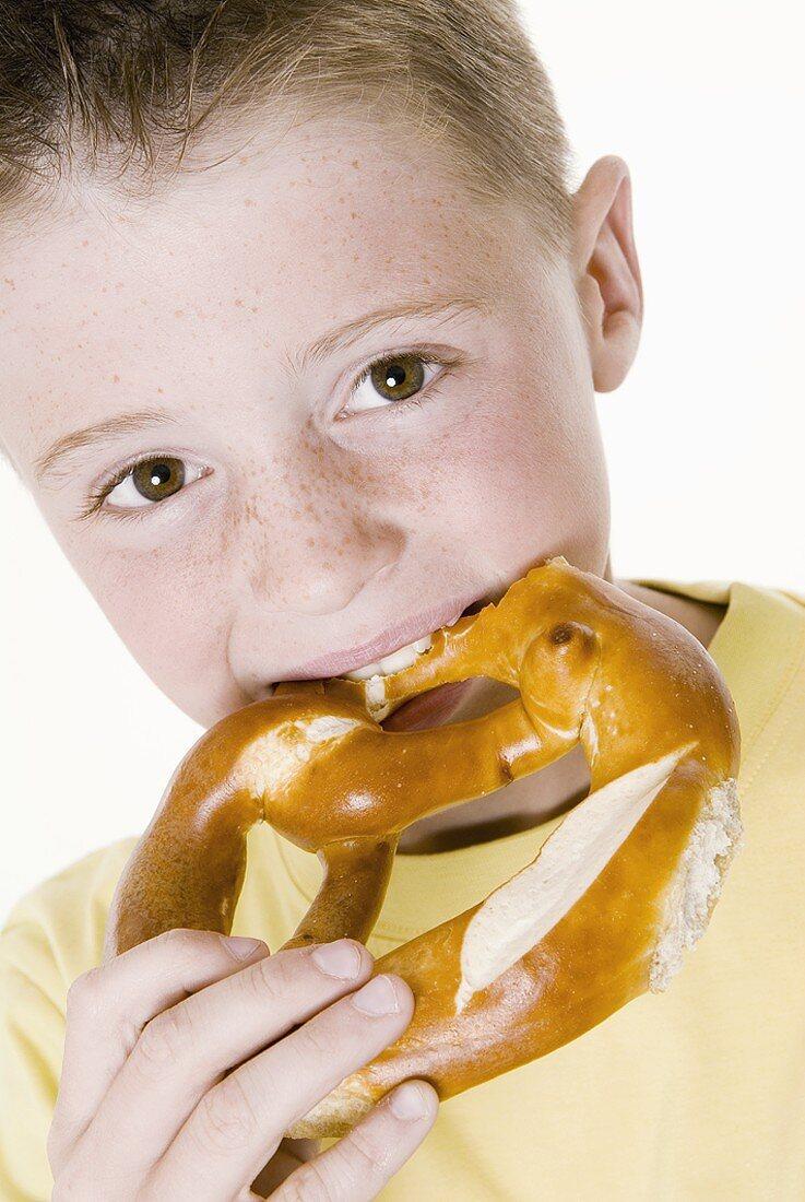 Boy biting into a pretzel